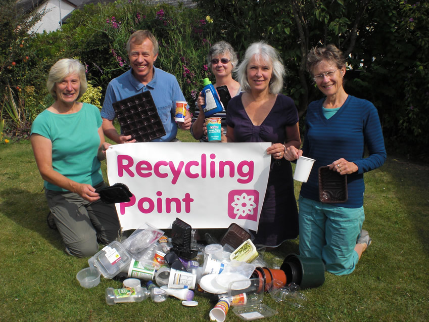 Photograph of a group of people with a pile of rubbish holding a Recycling Point poster