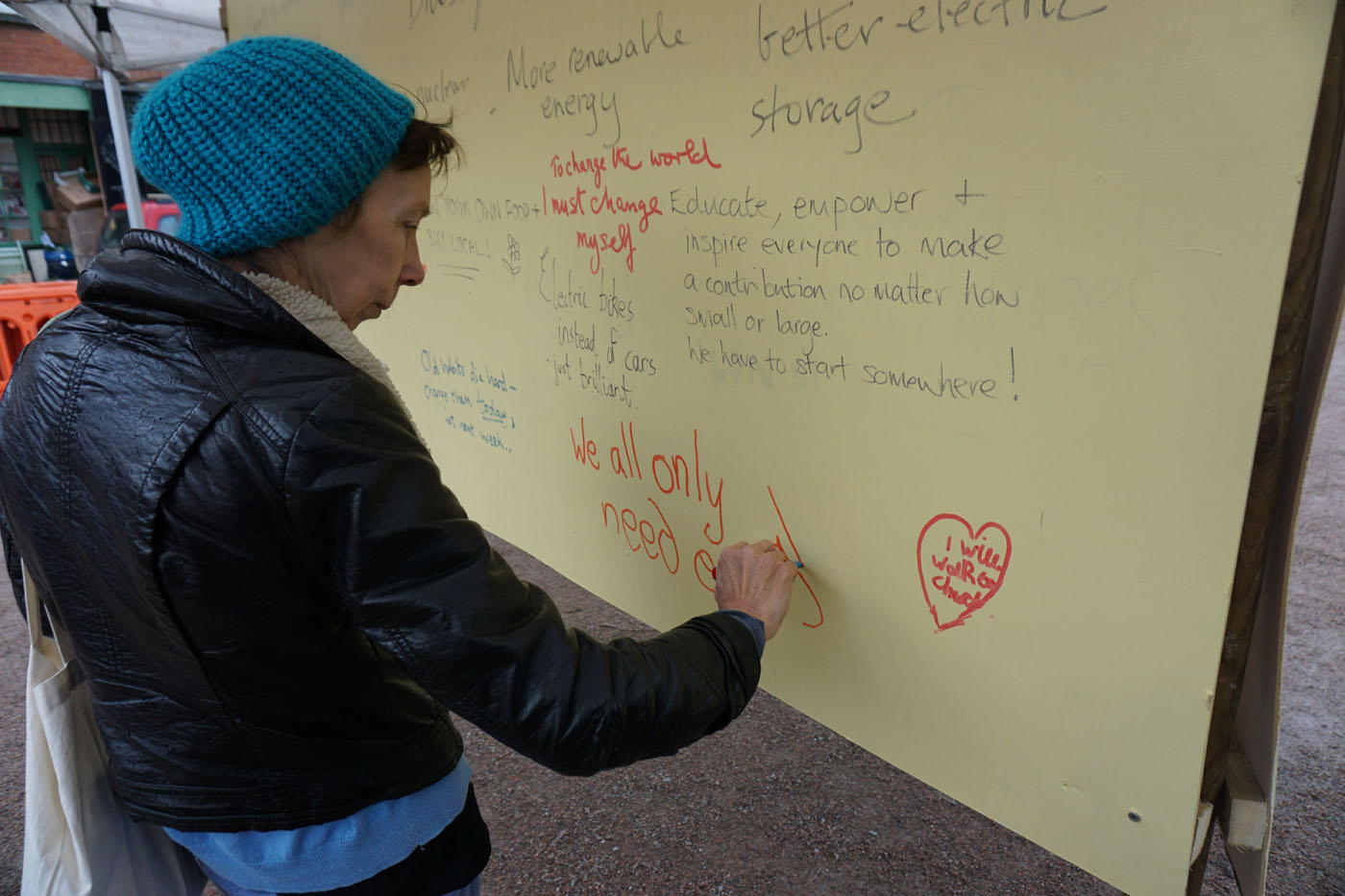 Photograph of a man writing on the graffiti board
