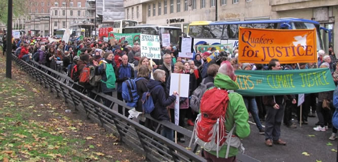Photograph of crowds of people in Park Lane led by climate justice banners