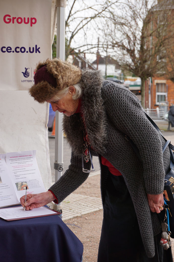 Photograph of a woman signing the Food Group petition against supermarket food waste