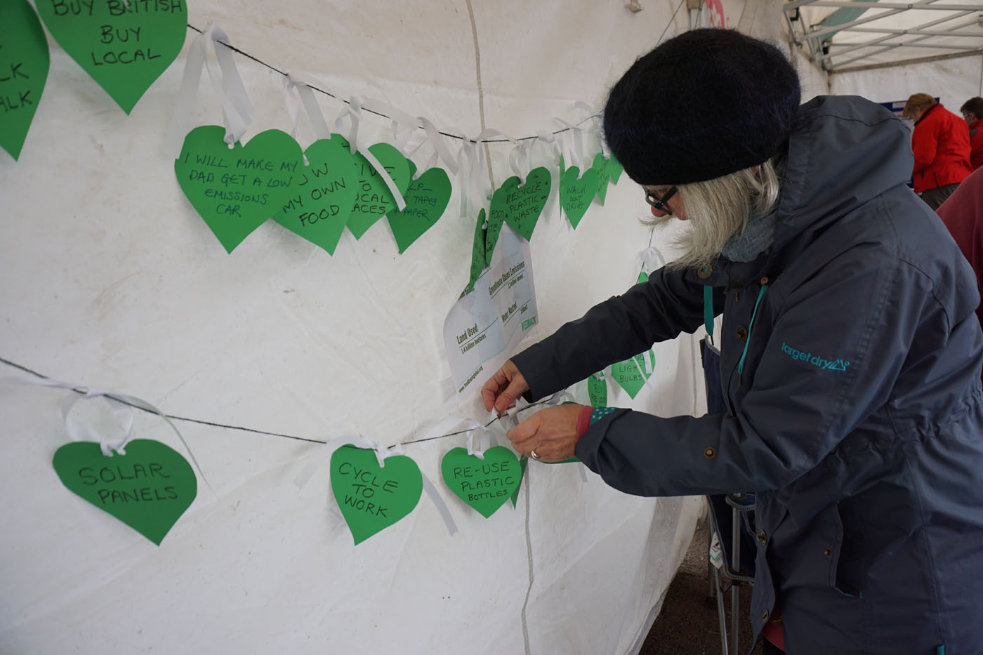 Photograph of a string of pledges written on green hearts
